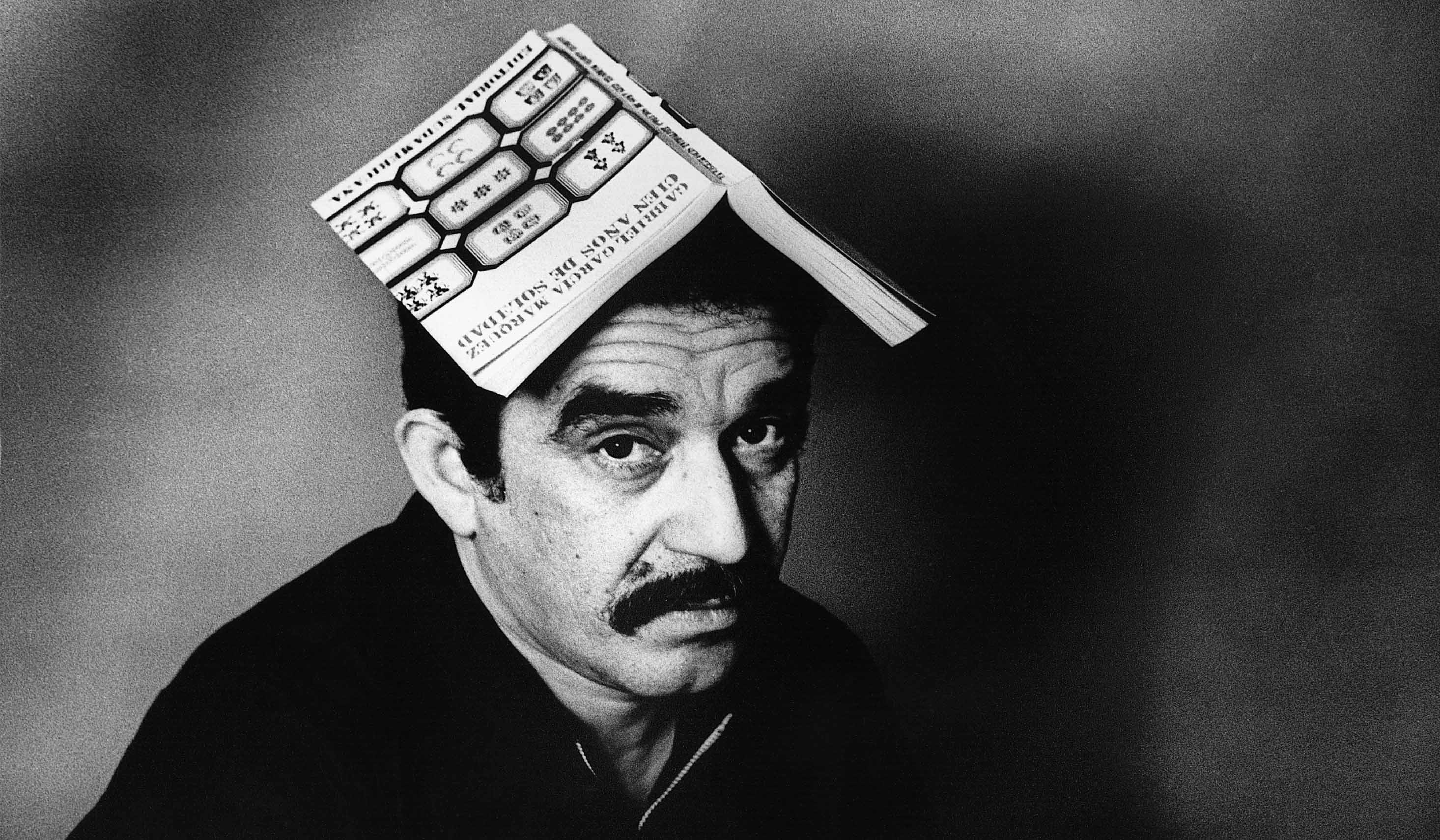 1975, Colombia --- Nobel-prize winning author Gabriel Garcia Marquez sits with a copy on his book One Hundred Years of Solitude) open on his head. --- Image by © Colita/CORBIS